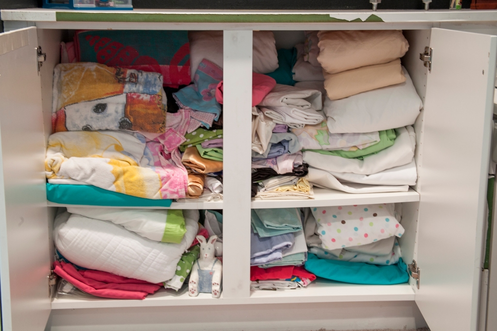 Now for the inside! Aughhhh! Right? It's been about five years since I cleaned this cabinet out. I just keep shoving stuff into it. I refolded and through out the old sheets we haven't used for years. I also packed up my older daughter's sheets for her own place.